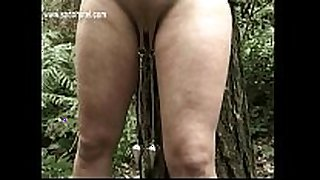 Slave fastened to a tree with got pulled on her nip...