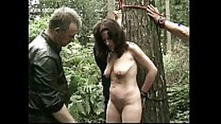 Naked slave bound to a tree got her pierced puss...